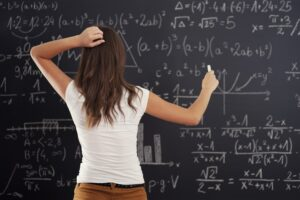 Girl Doing Math Problem On Chalkboard