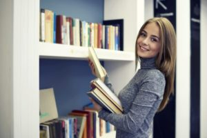 Student Holding Literature For Online Course