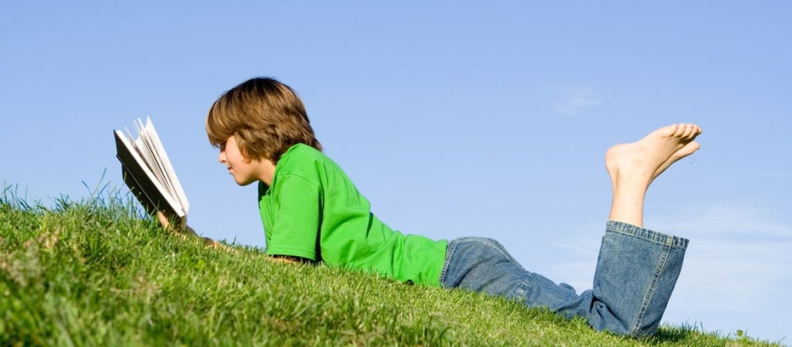 Boy Reading Outside In The Grass