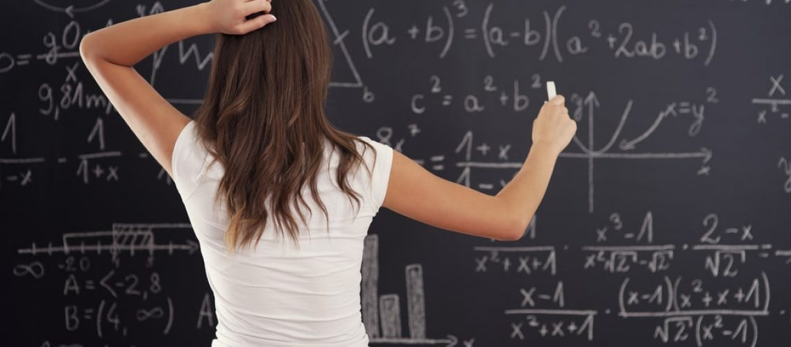Girl Doing Math Problem On Chalkboard