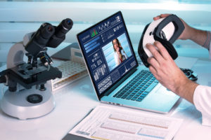 pair of hands using a virtual reality laptop and biology class equipment